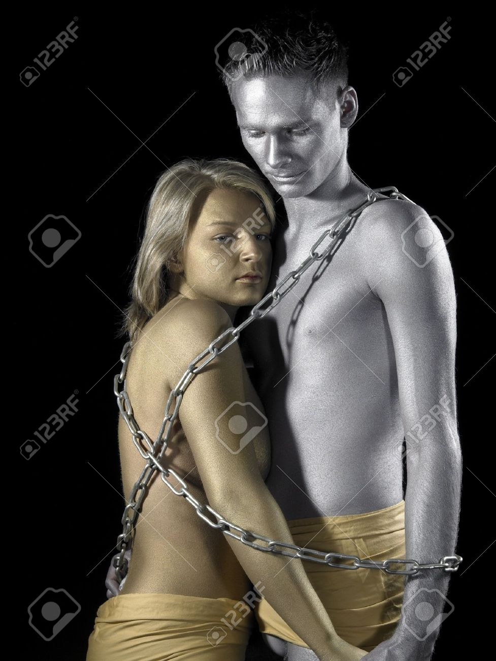 studio photography of a gold and silver bodypainted couple in chains Stock Photo - 11402874