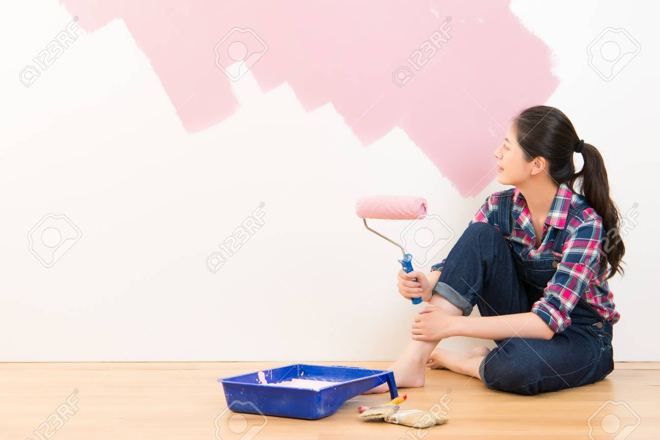 Happy Smiling Woman Painting Interior Wall Of New House Multicultural