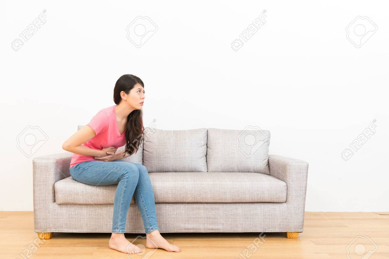 uncomfortable couch. Stock Photo - Young Woman Sitting On Couch Sofa Making Stomach Pain Gesture And Feeling Uncomfortable In The Wooden Floor With White Background.