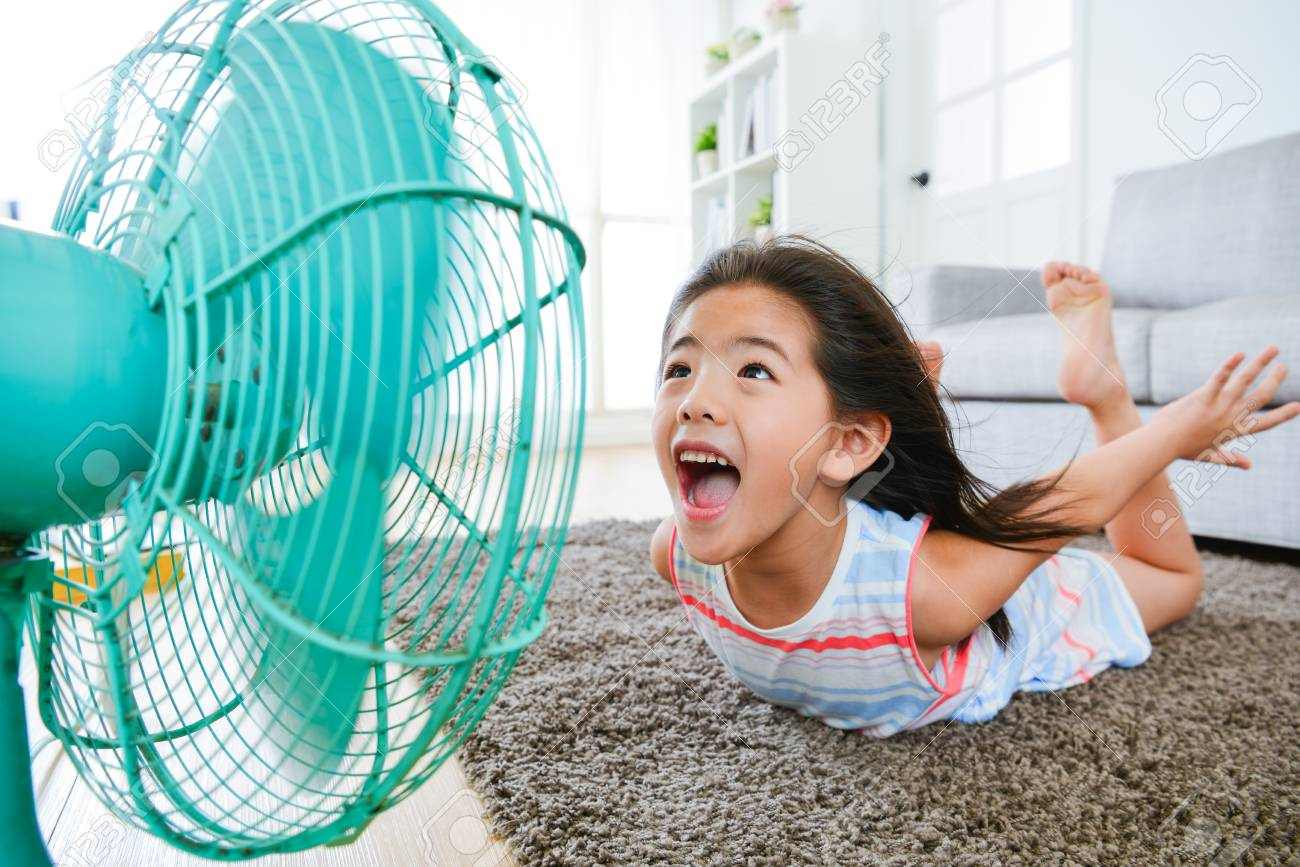 sweet beautiful little children lying down on living room floor and face to electric fan enjoying cool wind with flying posing with selective focus photo. - 83257947