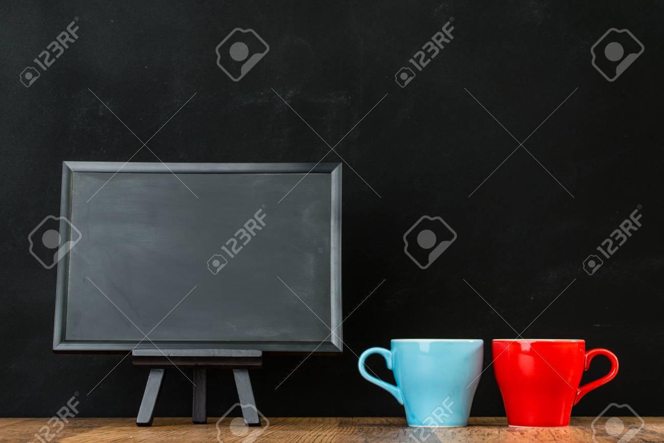 Parete Dipinta A Lavagna lavagna dipinta gesso su sfondo nero muro con disposizione tazze di caffè  rosso blu presentato sul concetto retrò di prestazioni pavimentazione in