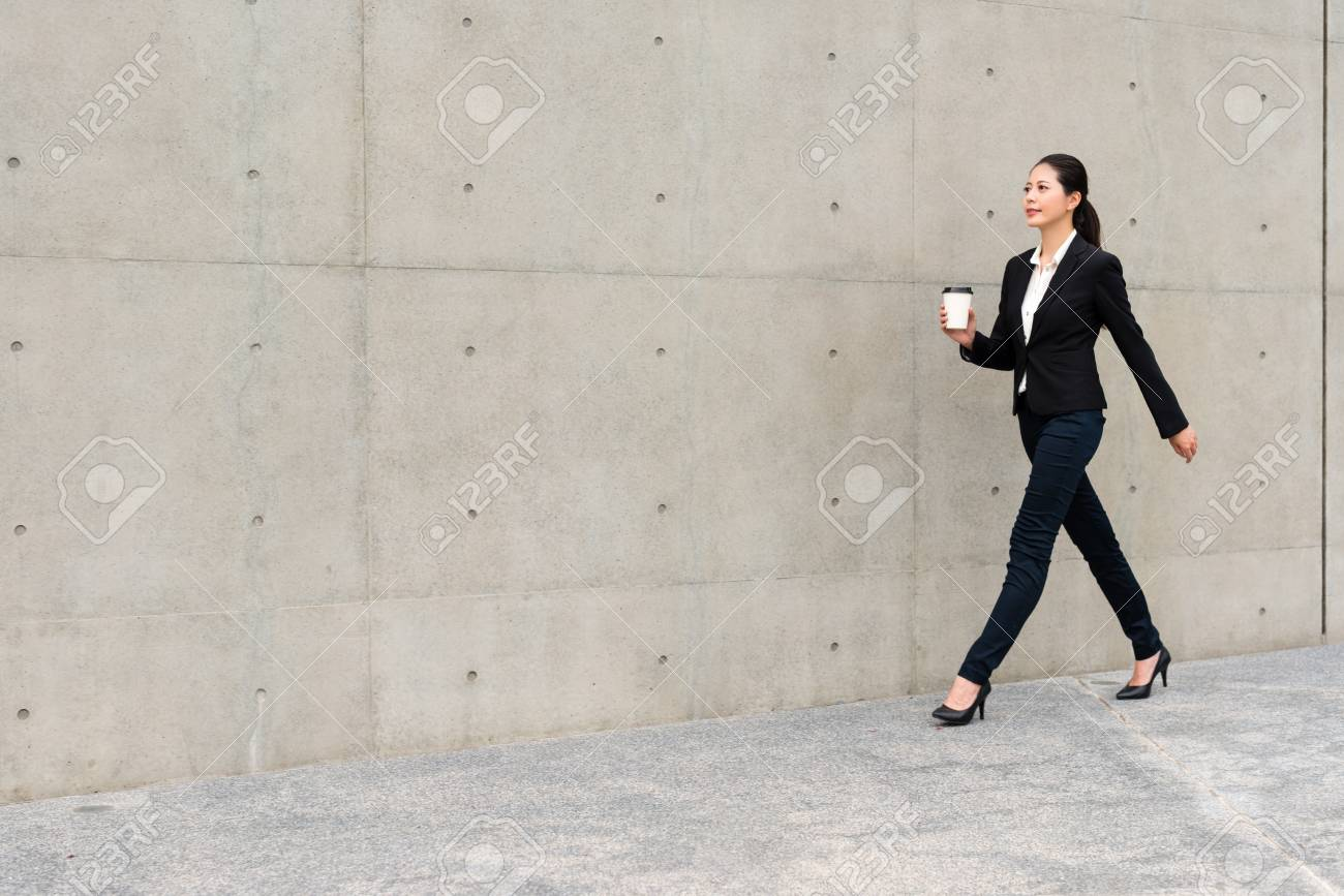 Beautiful suit right woman holding white coffee paper cup walking beautiful suit right woman holding white coffee paper cup walking in office outside gray wall background voltagebd Images
