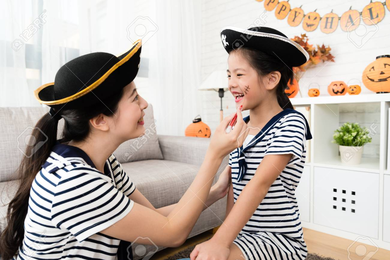 pirate girl and mother have fun with Halloween makeup drawing scars on the face at home - 85948802