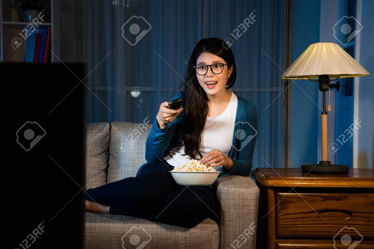 happy attractive lady eating popcorn and selection tv channel searching interesting movie sitting on sofa couch in living room at night. - 87808222