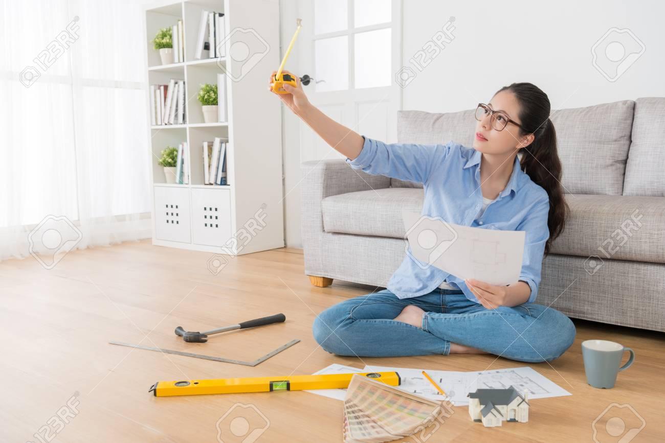 Schönes Selbstbewusstes Weibliches Haus Innenarchitekt, Der Im Wohnzimmer  Holzboden Sitzt Und Ingenieurbandmaßstab Hält, Der