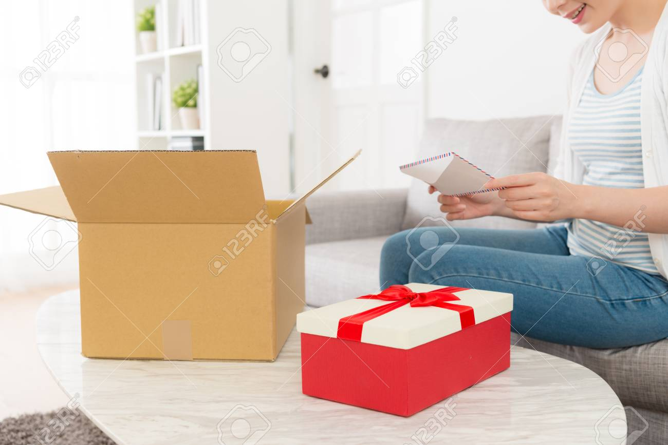 Young Elegant Woman Opening Delivery Parcel Box At Home And Getting
