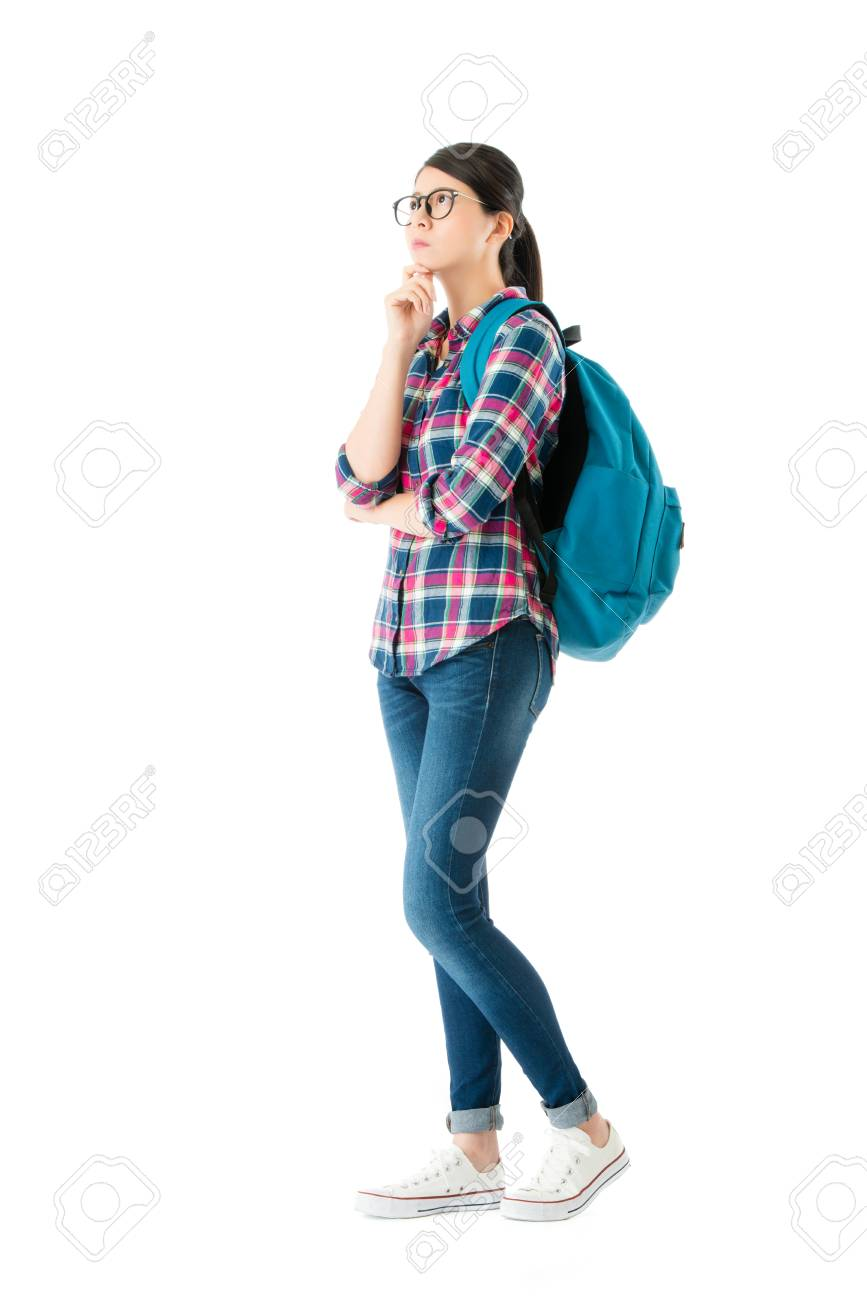 young pretty woman carrying school backpack standing on white wall background and thinking about education study problem solution. - 91976092