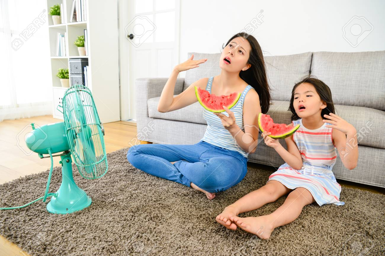 young mother with cute little daughter feeling hot in summer sitting on living room floor blowing electric fan refreshing and eating cold watermelon. - 93697830