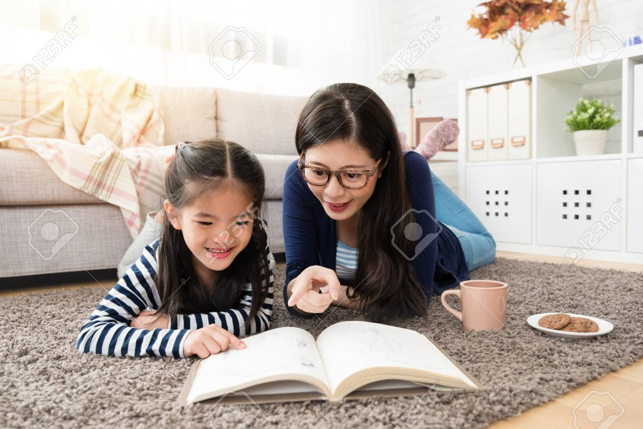 charming asian mother and her daughter reading book and enjoy