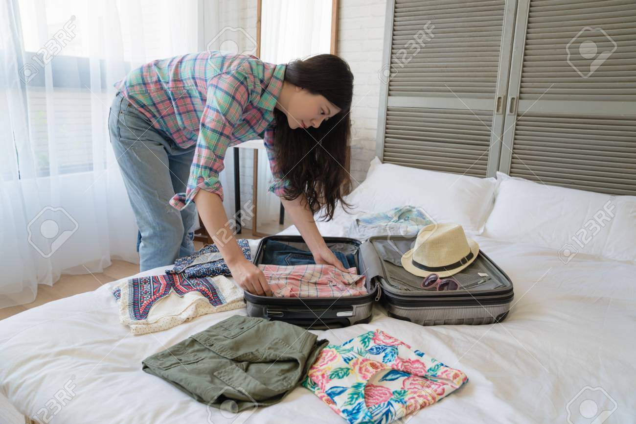 Side view of the Asian female tourist preparing her suitcase. She folded every clothes nice and neat. - 104440489