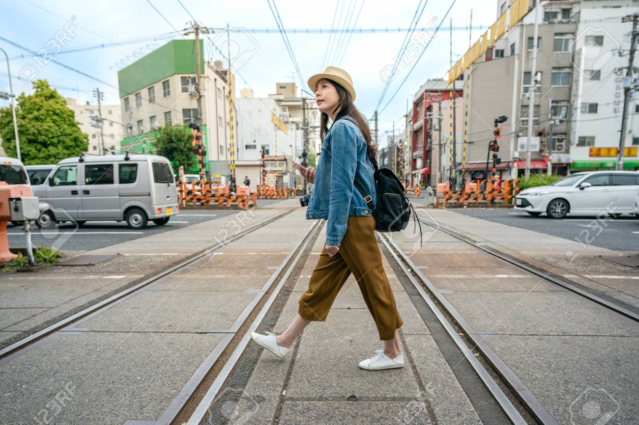 relaxed travel woman walking across the railroad holding her phone in osaka city in japan. - 107566375