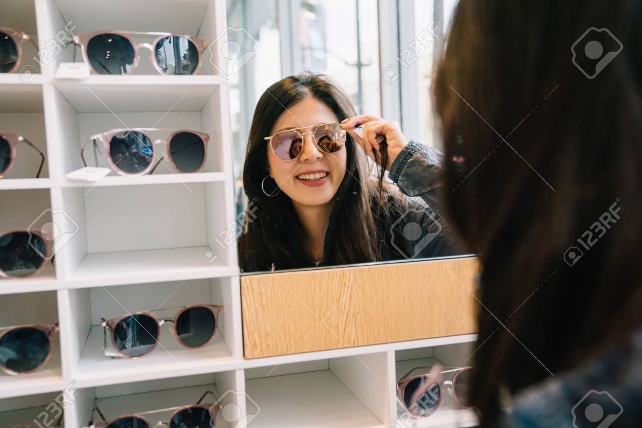 attractive woman trying sunglasses in the glasses shop and looking in the mirror. Asian lady shopping lifestyle. beautiful girl in suitable sunglasses. - 109943562