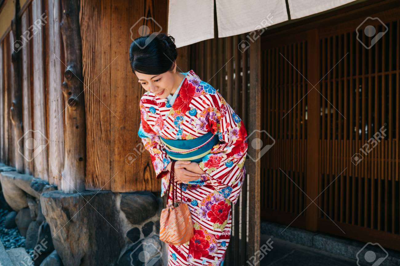 Japanese lady bowing in front of her house with beautiful kimono. traditional lifestyle in jp. attractive woman with colorful kimono clothing in summer. - 115081873