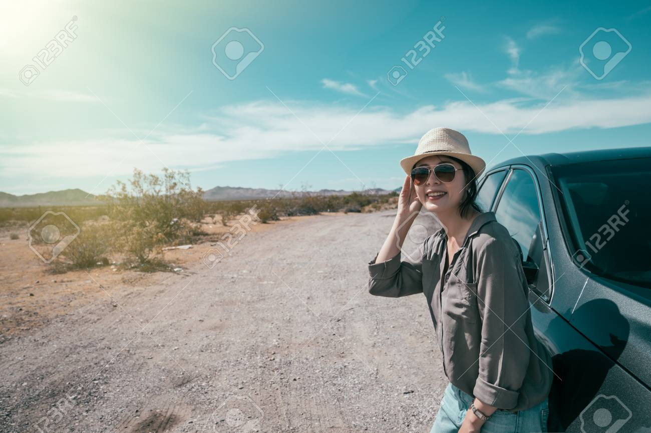 female car driver standing on the empty nature sunny day relying on the black car. young woman with straw hat and sunglasses enjoy the beauty of the wild during the trip. asian lady self driving tour - 112052296