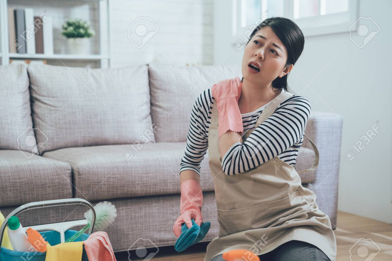 painful woman with shoulder hurts because of doing lots of house chores. young lady sitting on floor massage herself with a sick face holding blue rag with cleaning product in bucket nearby. - 112722761