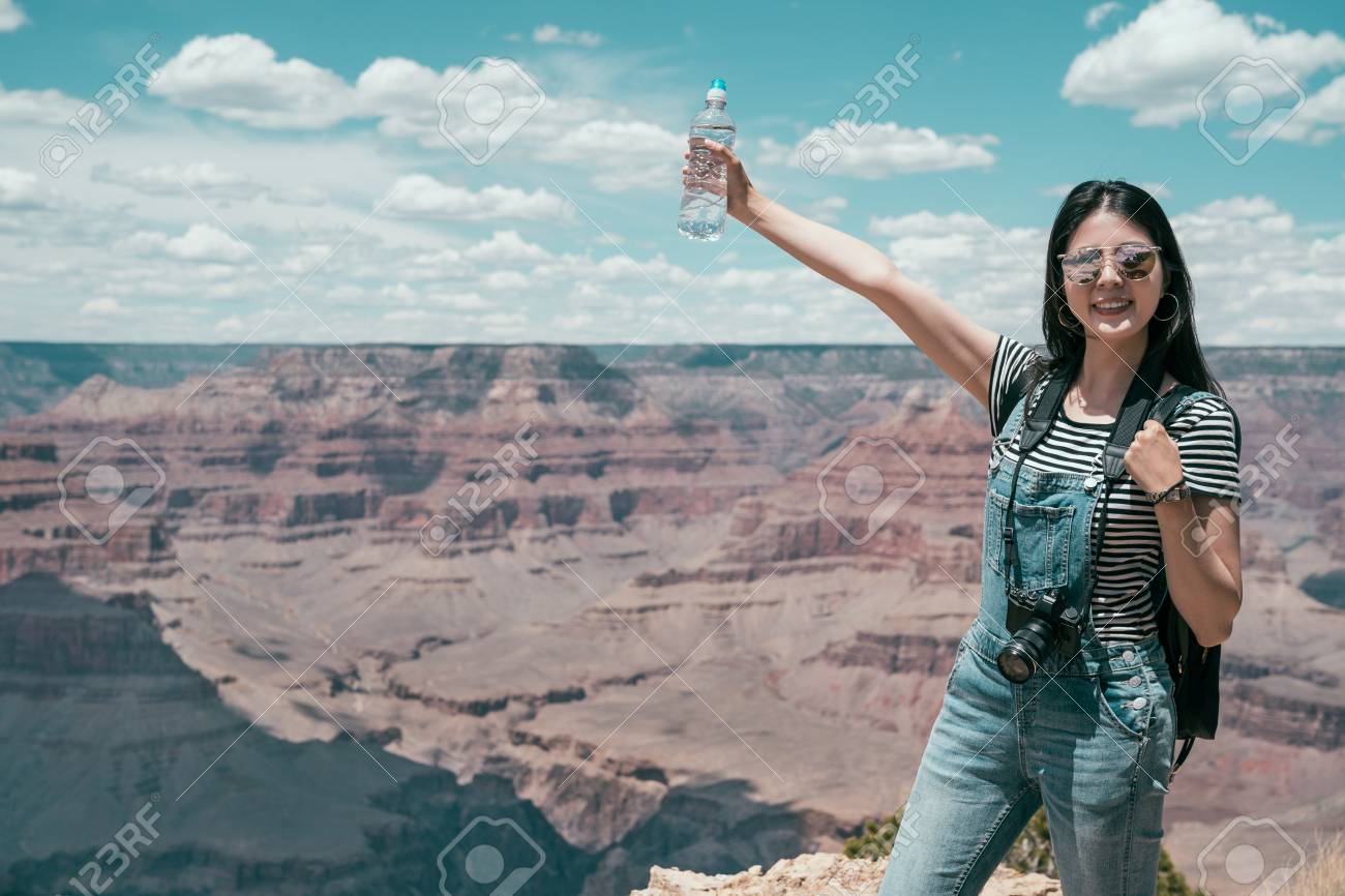 carefree young lady traveler relaxing standing on the top of skyline on summer vacation. woman hiker happy showing bottler water raising hands on grand canyon national park. female tourist joy trip. - 112721218