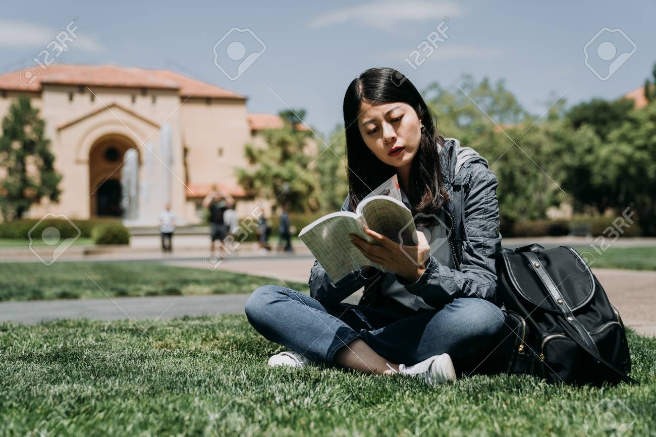 Portrait of happy charming asian woman reading a book outdoors in university. - 116014822