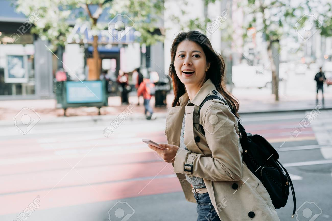 travel female backpacker holding cellphone searching route on