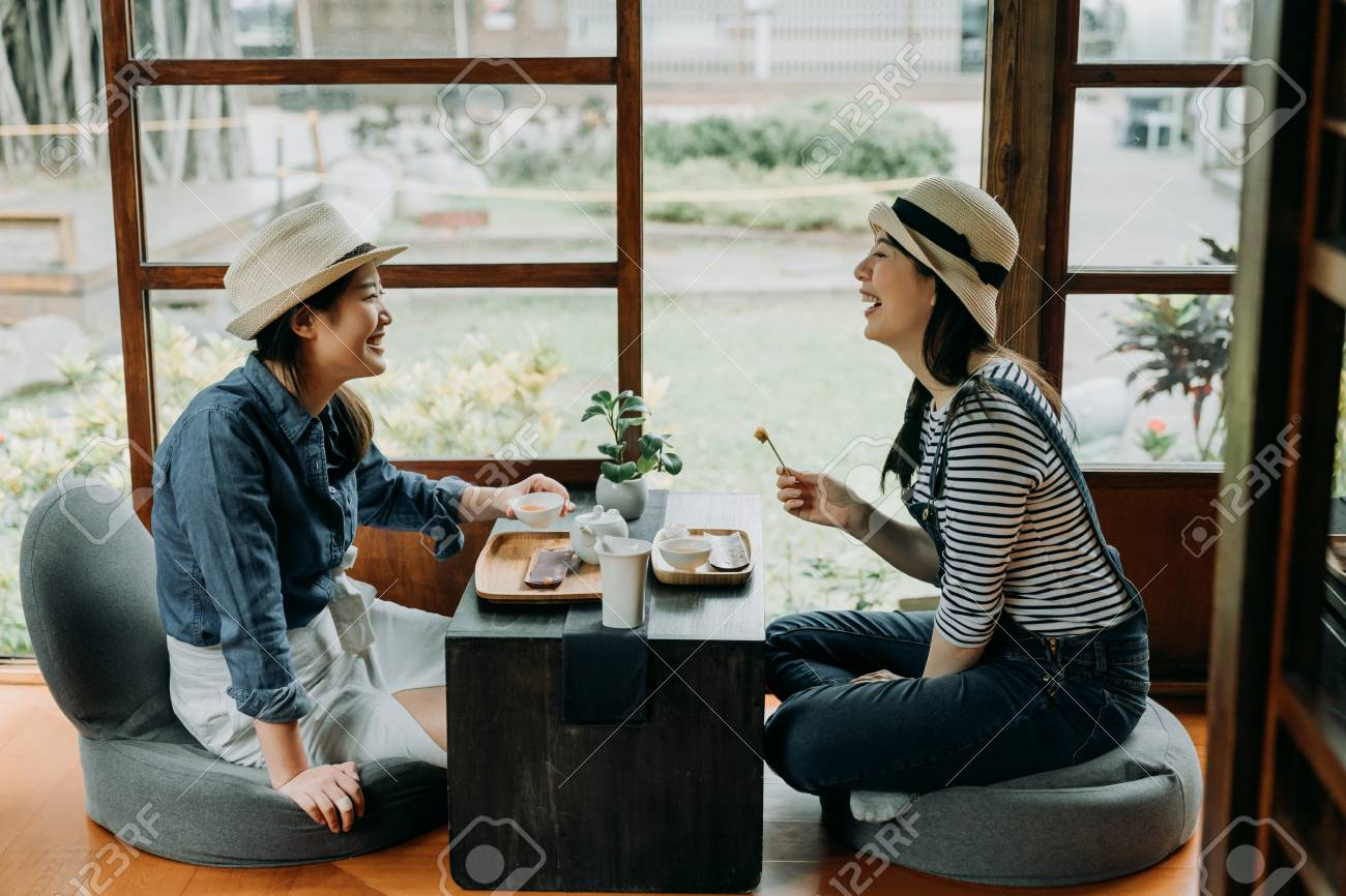 two girlfriends laughing with jokes drinking matcha having tea ceremony experience. - 119599390