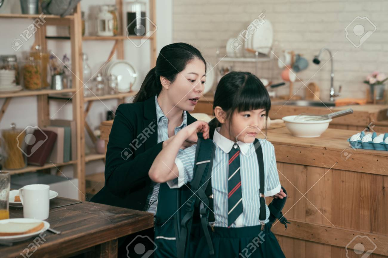 young mother worker in business suit help daughter get ready for school. Mom support child to wear backpack bag in wooden kitchen talking nag to little girl after breakfast time leaving home to study - 122008946