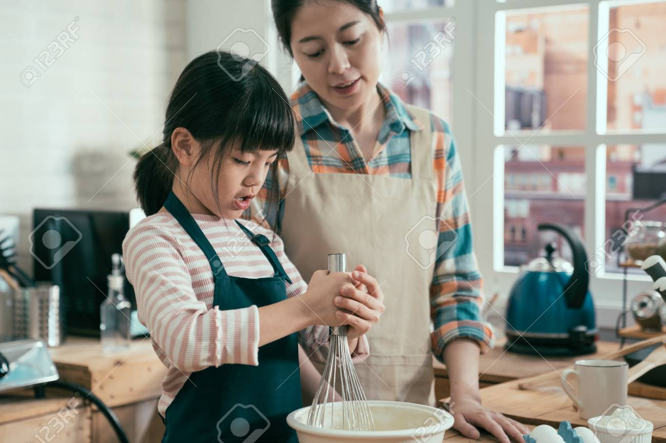adorable kid with mom mix flour and egg together in bowl at home. - 121830349