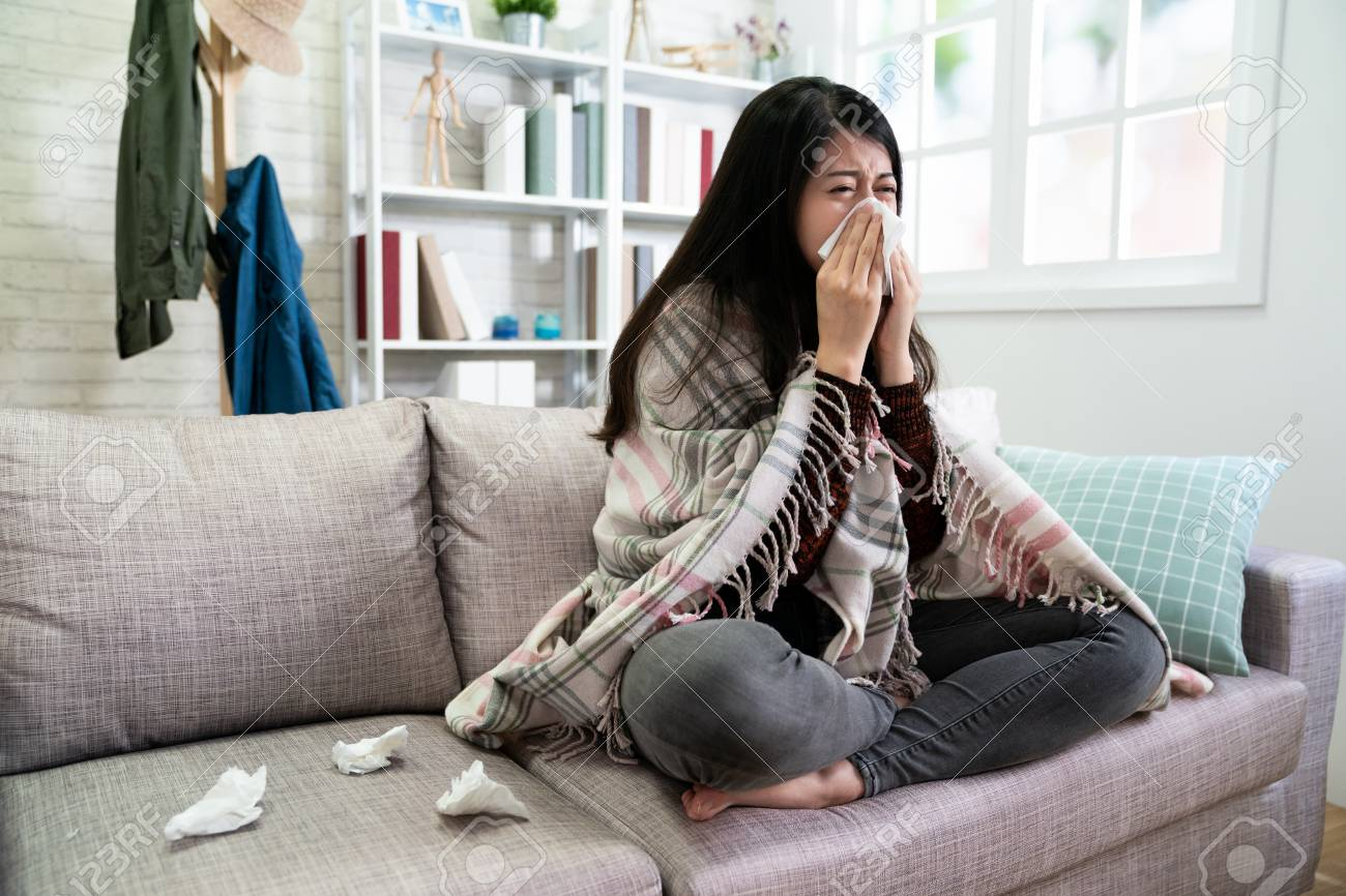 asian illness lady with seasonal infections flu and runny nose using tissue on sofa at home. - 121830453