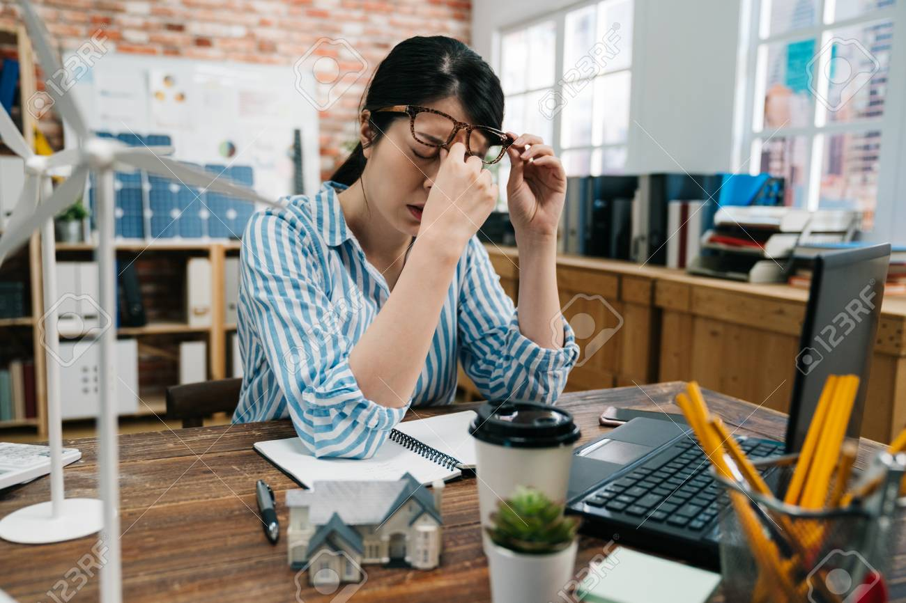 Young elegant asian architect woman in glasses tired rubbing nose and eyes feeling fatigued and headache. Stress and frustration concept overworked on construction plan of green economy building. - 121817121