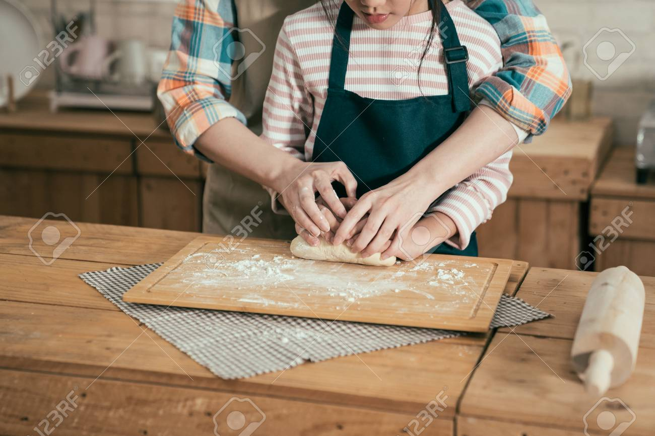 happy family time parent kid diy baking cake in kitchen on mothers day. unrecognized asian woman mom teaching child daughter kneading dough for bread on easter. close up female and little girl hands - 123140773