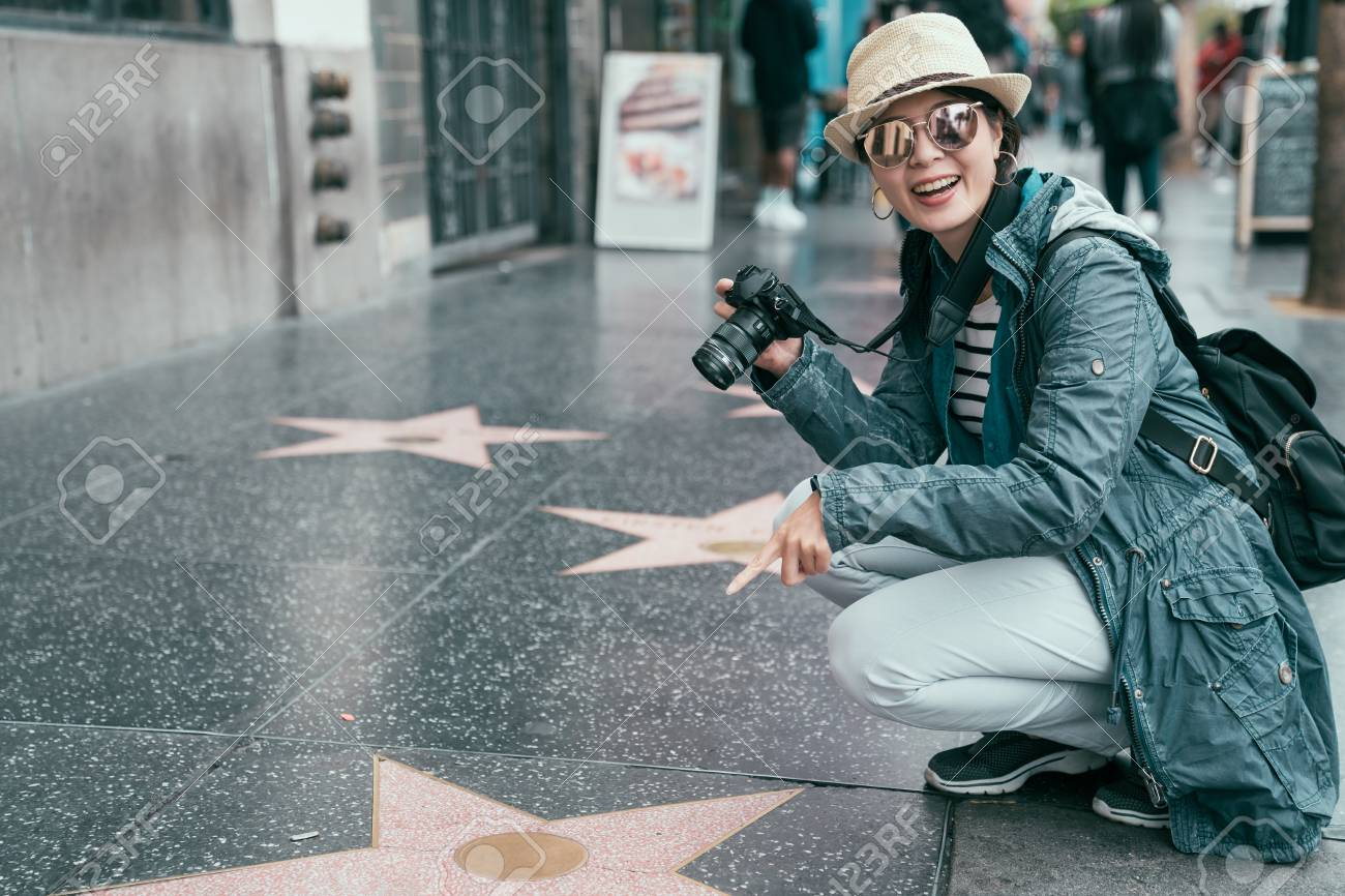 asian female tourist finger pointed star plaques of honored celebrities on Hollywood Boulevard in Los Angeles on sunny day. woman backpacker kneeling down on walk ground showing camera smiling - 122715426