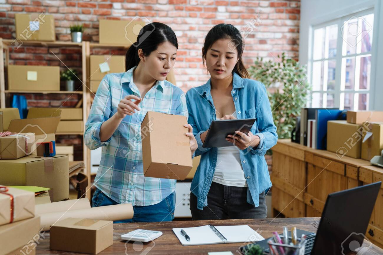 Young women teamwork partners packing order into box together using touchpad to do delivery to client. two asian female colleagues with tablet checking goods number and prepared cardboards in office. - 123194259