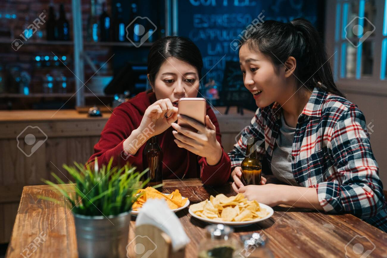 two beautiful girl best friends drinking beer using smartphone and smiling while resting at pub in night. group of asian women having fun gossip browsing website social media on mobile phone joyful. - 124266312
