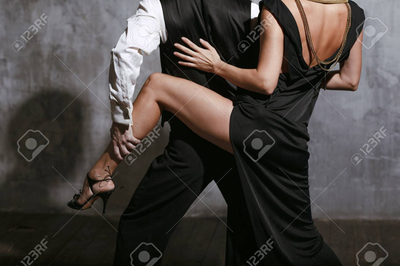 Young pretty woman in black dress and man dance tango - 99093389
