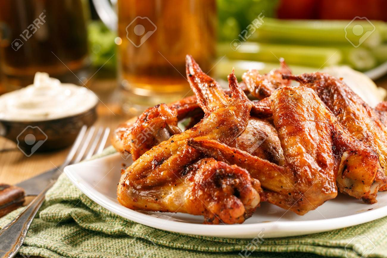 Roasted wings on the plate with sauce and beer on background, close-up. - 37696018