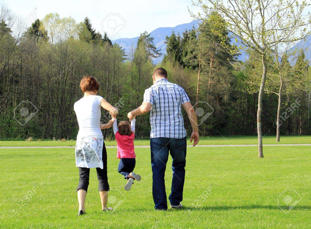 Having fun in the spring park; young child and her parents Stock Photo - 13611742