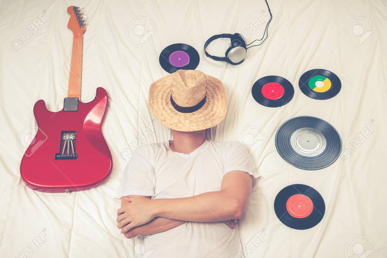 Man Sleeping On Bed With Records Headphone And Electric Guitar