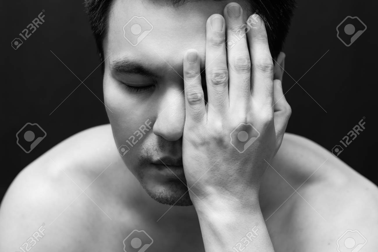 Asian handsome man in black and white emotion portrait photo feel sad headache and