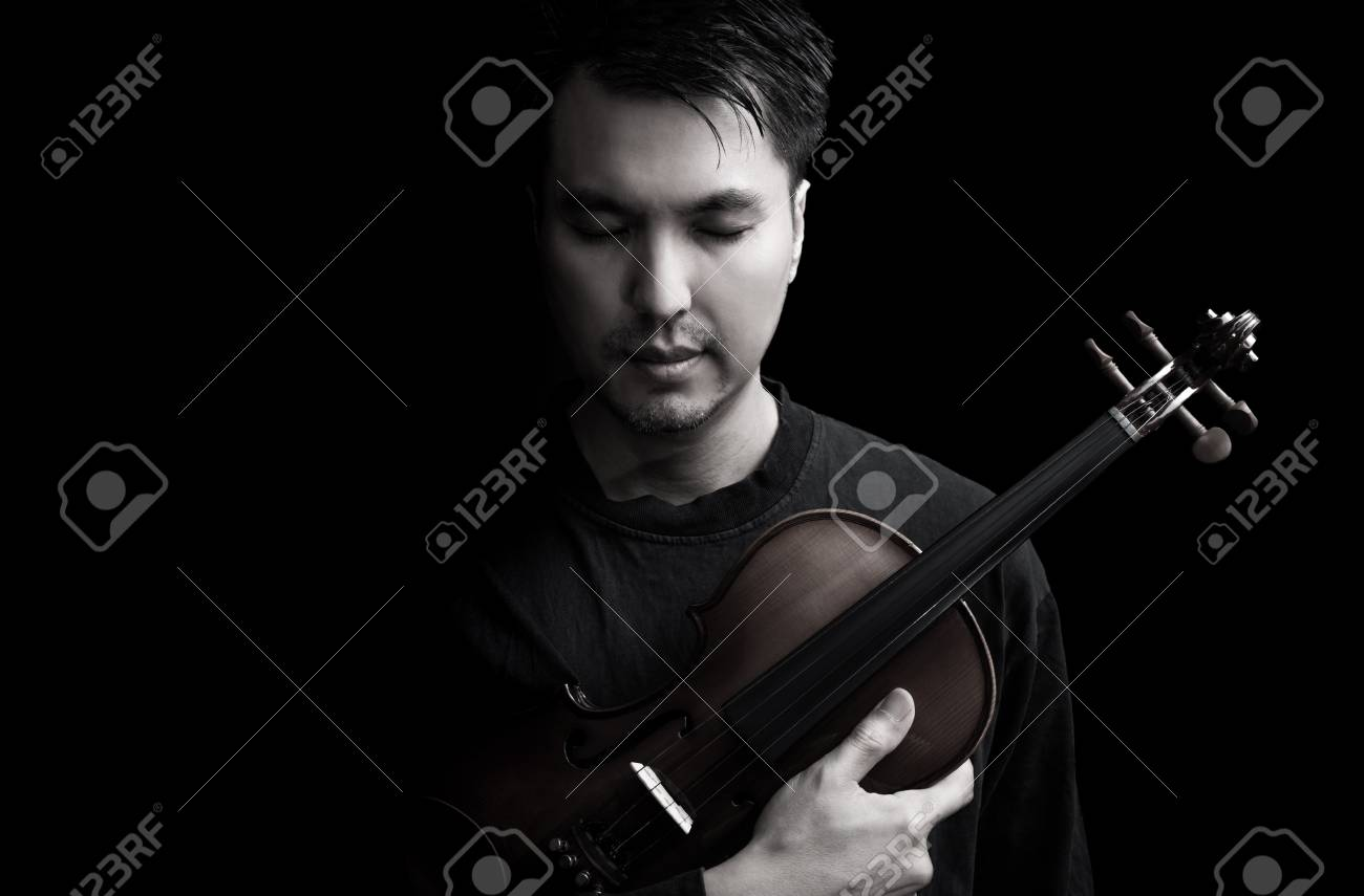 Emotion portrait of asian handsome musician posing on violin isolated on black stock photo