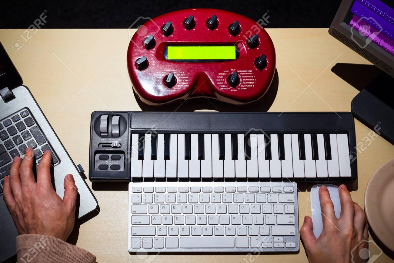Mains de compositeur masculin utilisant un ordinateur clavier midi