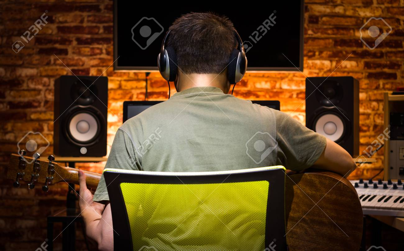 back of asian male musician recording acoustic guitar and jamming