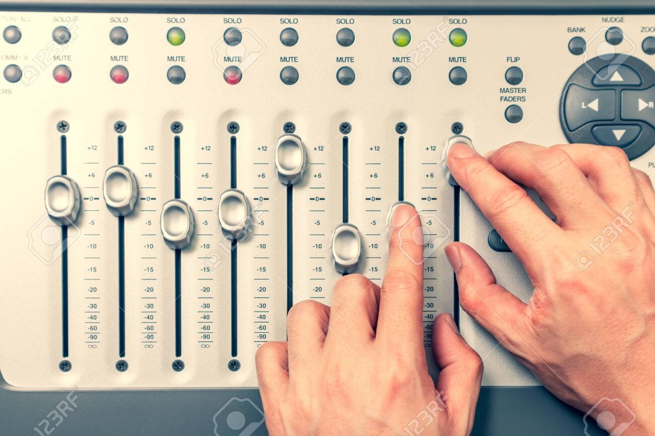 sound engineer hands adjusting volume level fader on digital