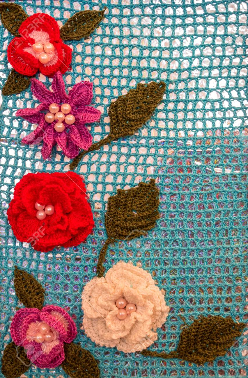 Beautiful Crocheted Flowers On A Blue Background Stock Photo