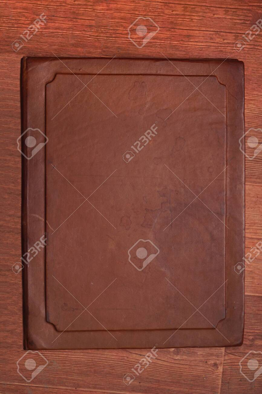 Antique brown aged leather cover with different spots on a wooden brown background - 145073254