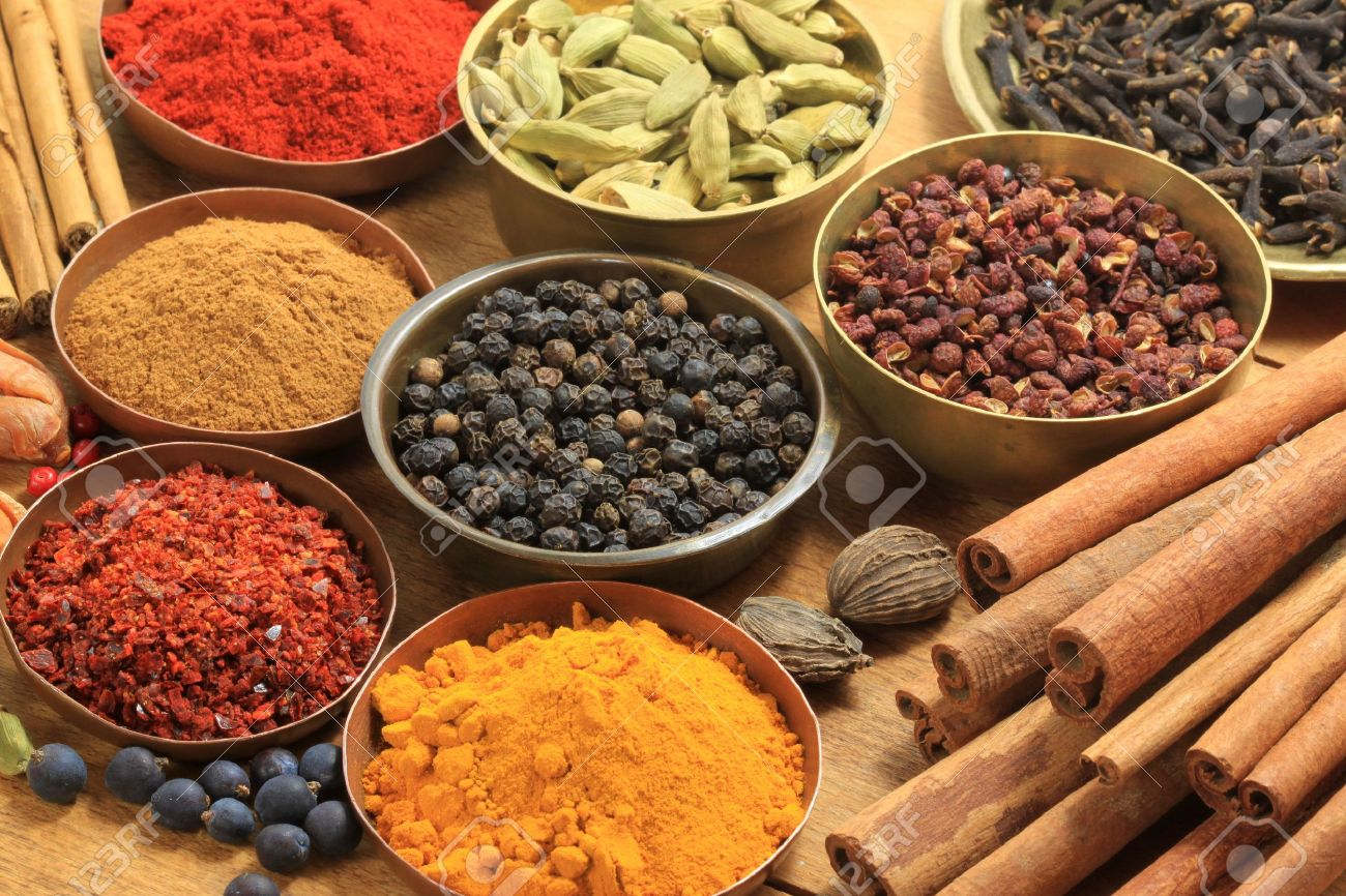 Cooking ingredients - warm colours of herbs and spices. Cinnamon sticks, cardamon, allspice, clove, mace, fenugreek, coriander and juniper Stock Photo - 7948814