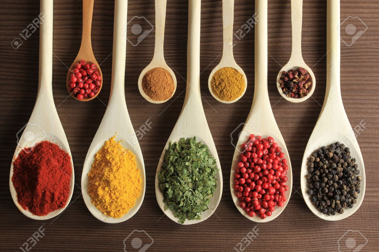Colorful spices in wooden spoons - beautiful kitchen image. - 9418849