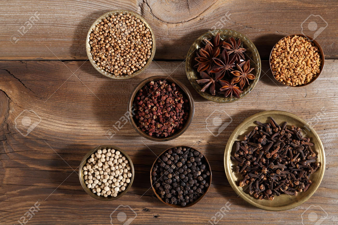Brown aromatic spices in metal bowls on a wooden background. Top view. - 146162078