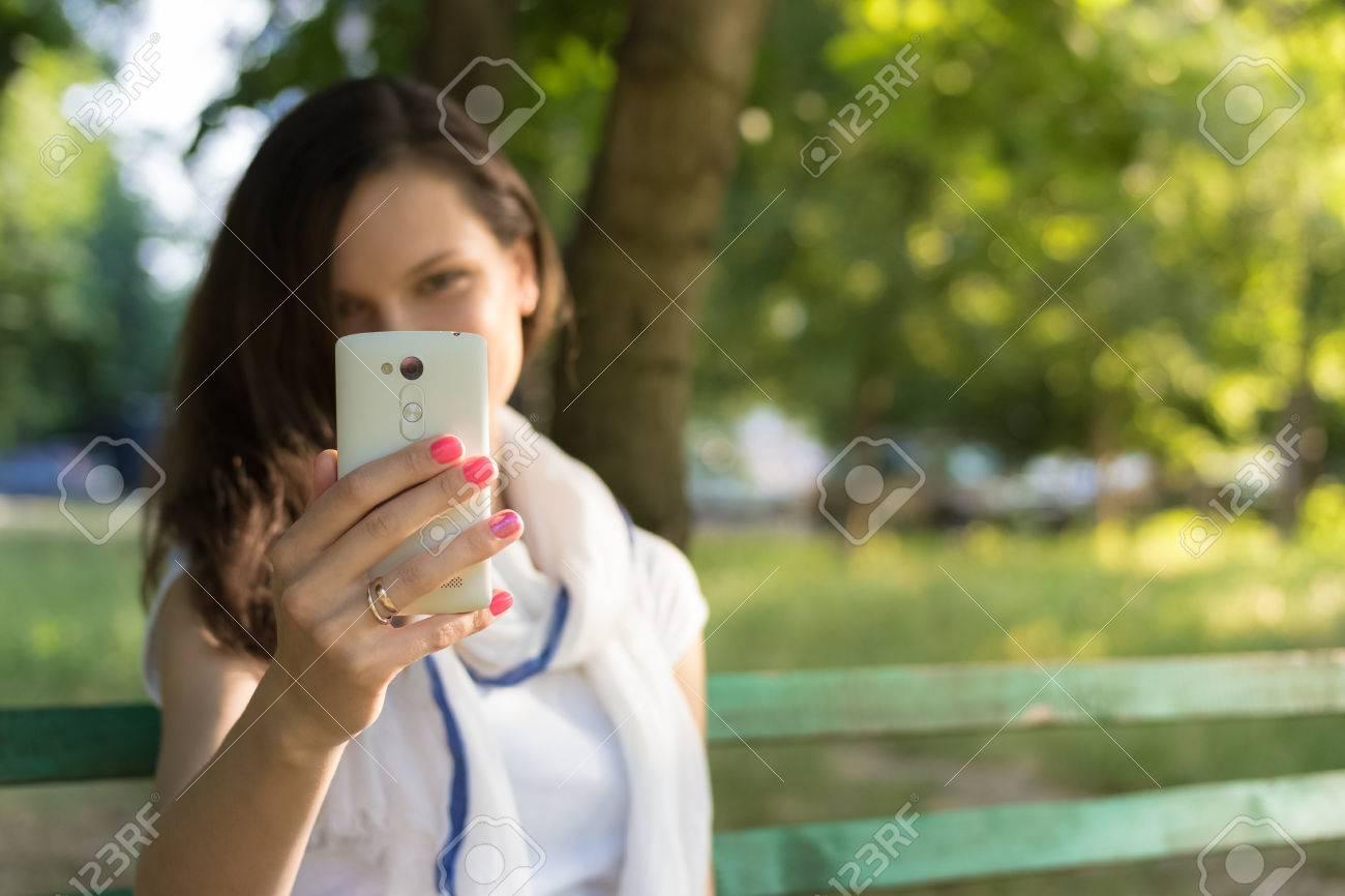 Alegre Mujer Joven Sentada En Un Banco Del Parque A La Sombra De Los ...