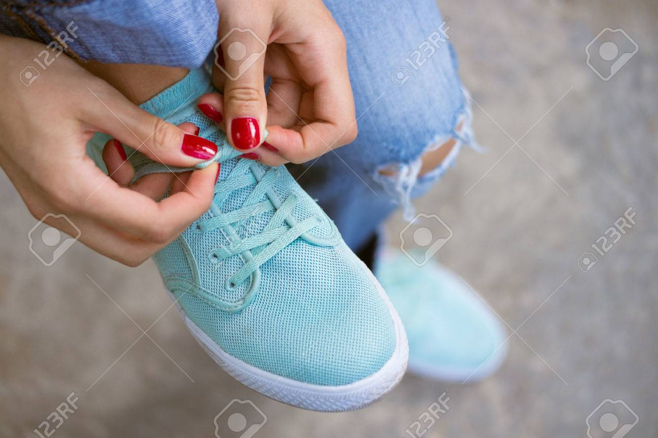 Female hands with a red manicure knotted laces on sports shoes. Young woman in blue jeans walking outdoors when she untied shoelace. A walk in the city. - 43196144