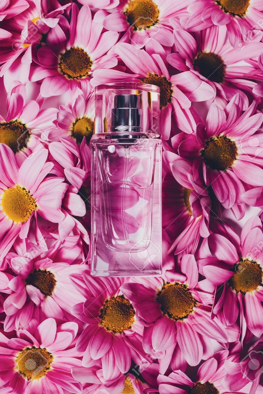 Vertical Image Of Transparent Perfume Bottle On Purple Flower
