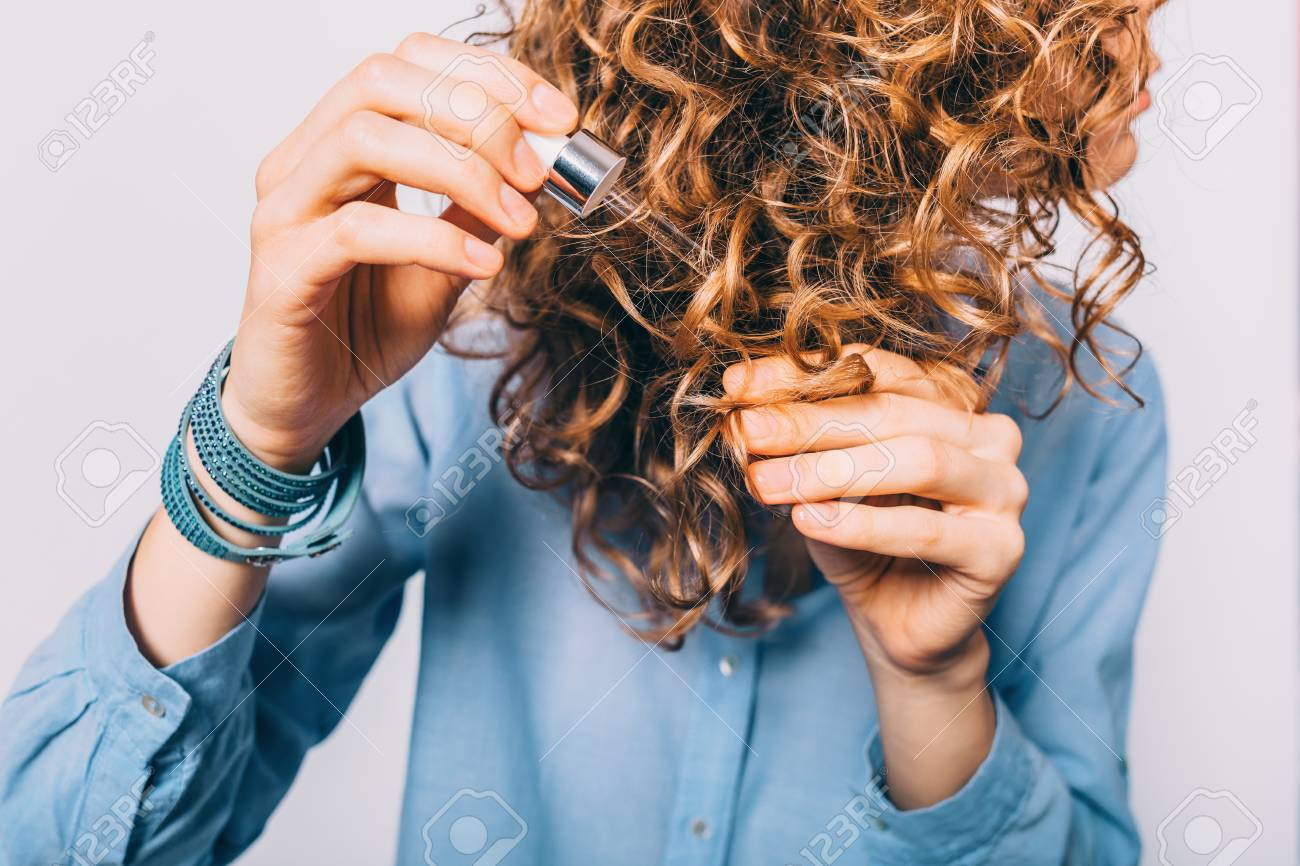 Young Woman In Blue Shirt Holding Her Curly Hair Tips And Pipette