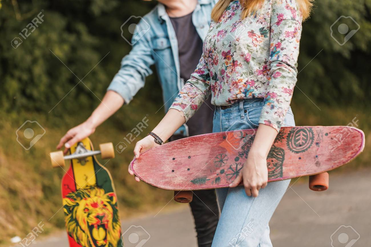 Boy and girl, hipster stylish teenagers wearing sunglasses are walking through the park holding skateboards in hands, teen freedom concept - 85041605